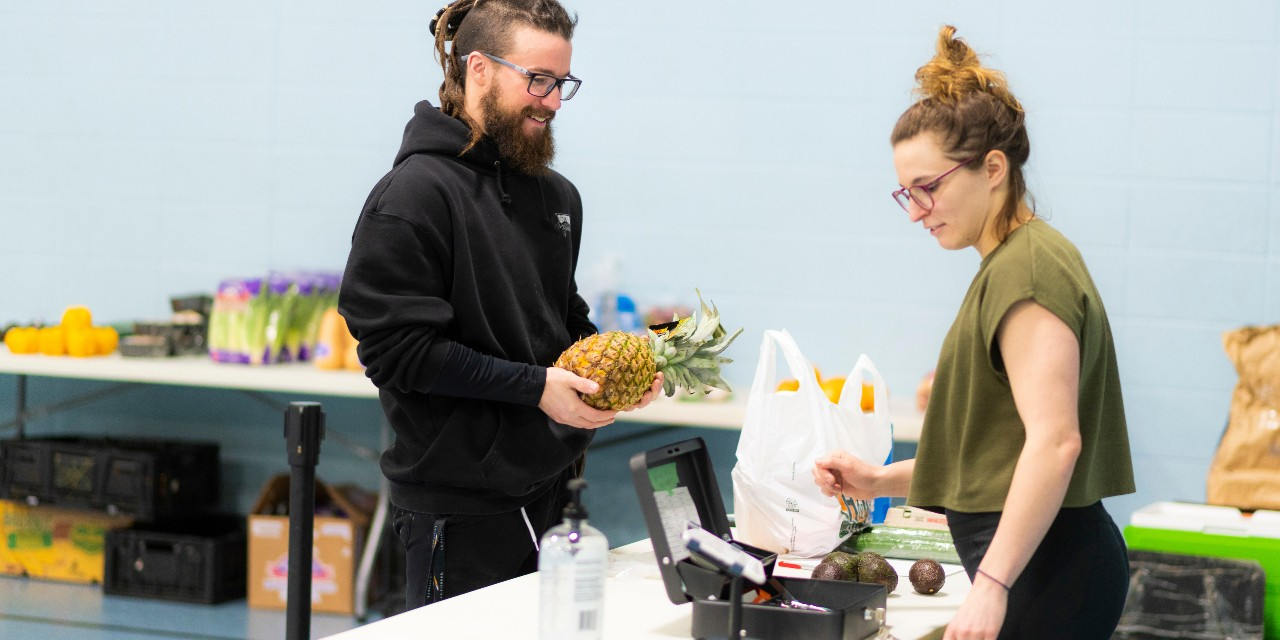 Ian Nason (left) and Monique Holowach, volunteers with the Grocery Run & Leftovers/Fresh Routes Community Partnership, help out at a grocery store in Trinity Christian Reformed Church in Edmonton. The partnership donates healthy food to 108 families weekly, and also runs a mobile grocery store to sell food to the community at affordable prices. (Photo: John Ulan)
