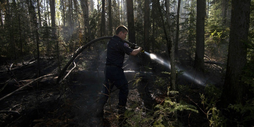 A Fort McMurray firefighter hoses down hotspots in the woods within the city limits. Rain will be a boon to the crews battling the fire but may pose challenges for water quality, say researchers. (Photo: Premier of Alberta, Flickr, CC BY-ND 2.0)