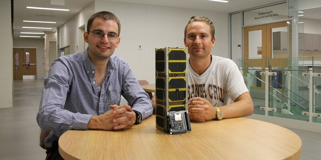 AlbertaSat team members Charles Nokes (left) and Tayler Robertson, with a model of their team's cube satellite, are preparing to participate in an international cube satellite conference.