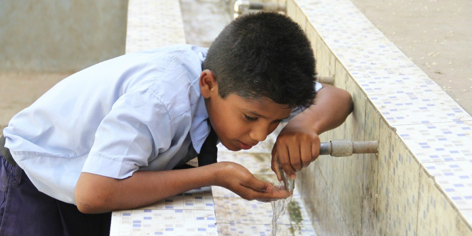 A young boy drinks from a water fountain in India. (Photo courtesy IC-IMPACTS).