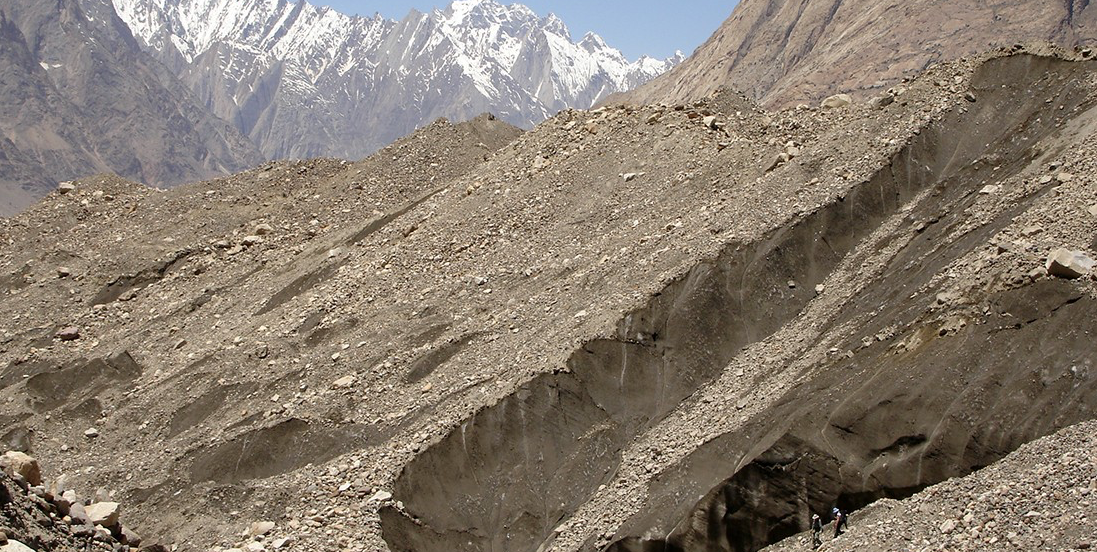 The debris-covered Baltoro glacier in Pakistan, with porters and scientists navigating the route. Thick debris, like that found on the Baltoro glacier, acts a shield to protect the ice from melting. Thin layers, however, are more likely to increase melting by attracting solar radiation. (Photo: Andy Bush)