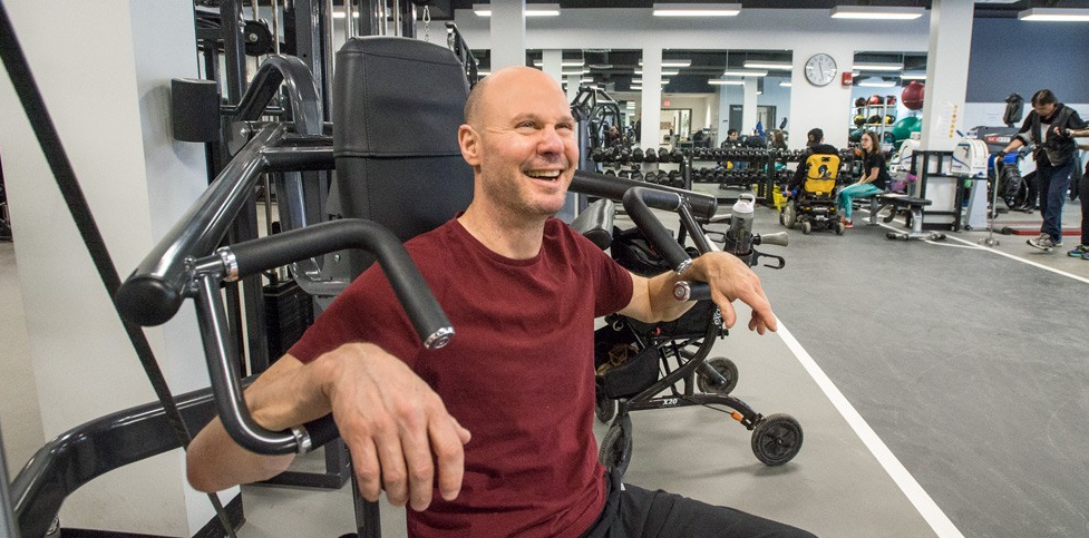 Bob Coyne lifts weights as part of his customized fitness plan at the Steadward Centre. Coyne, who has multiple sclerosis, says that even more than the physical improvement, the psychological transformation has paid the biggest dividends. (Photo: Richard Siemens)