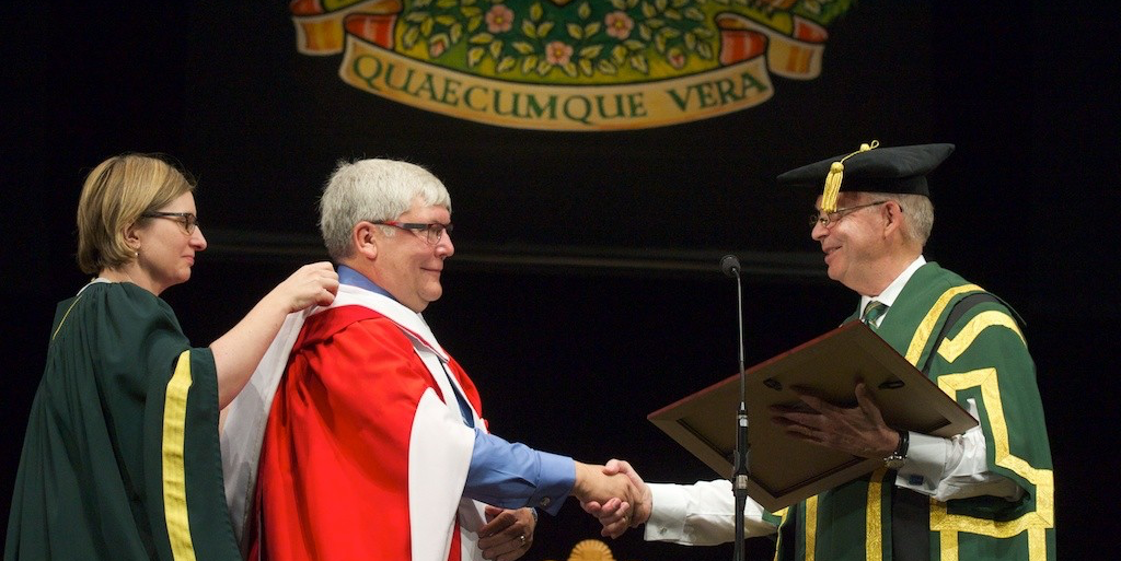 Dave Hancock receives his honorary doctor of laws degree from Chancellor Ralph Young during the convocation ceremony for the faculties of education and law June 3. (Photo: Richard Siemens)