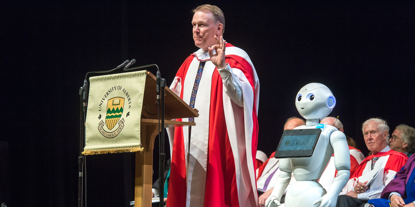 Dave Mowat, president and CEO of ATB Financial, is joined on stage by Pepper the robot after receiving his honorary doctor of laws degree June 7. (Photo by Richard Siemens)