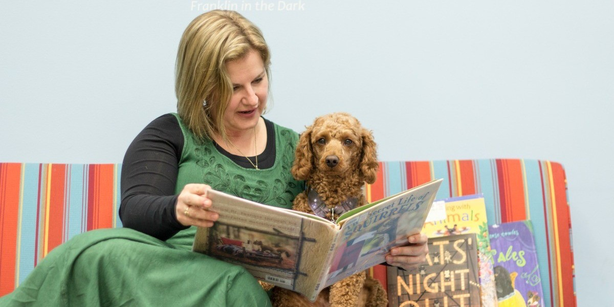 "Emily Bright Kennedy reads to Ruari, her young ""classroom dog in training."" Kennedy has seen the power of the human-animal bond in the classroom and in her own life."