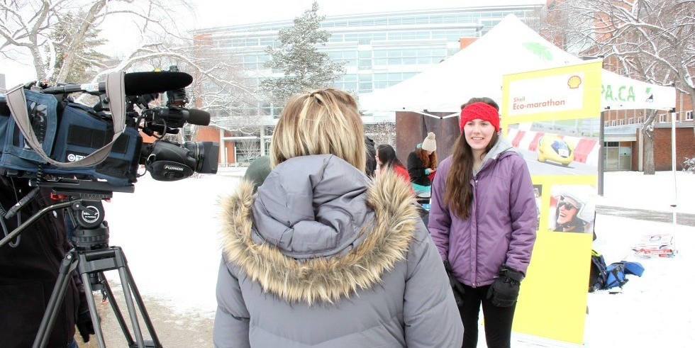 Engineering physics student Natasha Pye (right) gives a media interview about the U of A EcoCar. She played a key role on the EcoCar Team this year, earned a perfect 4.0 GPA and is one of two winners of the prestigious C.D. Howe award.
