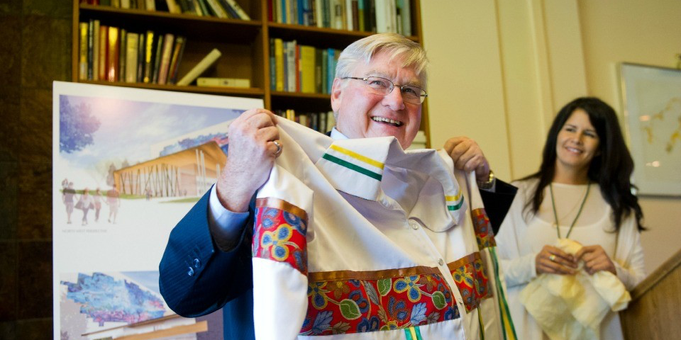 Eric Newell receives a ribbon shirt from Tracy Bear in 2012 in recognition of his work with Aboriginal groups. (Photo: Ian Jackson)