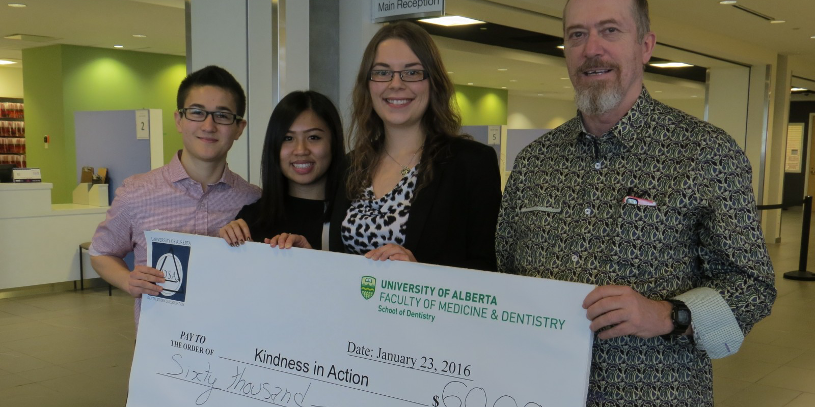 First year School of Dentistry students Nicholas Churchill, Brenda Pham and Emily Ervin present a $60,000 cheque to Kindness in Action vice-president Dave Maskell.