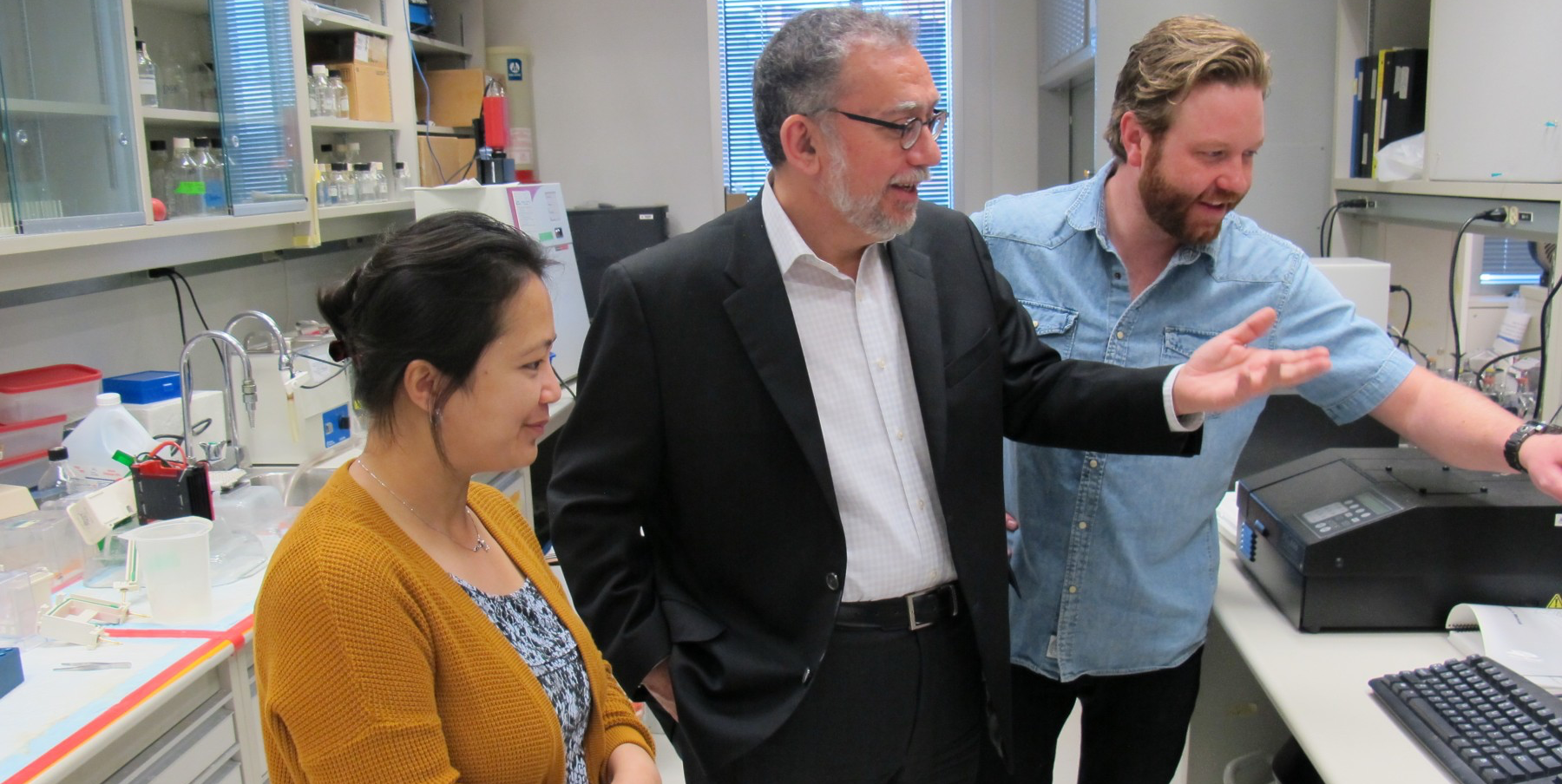 Harissios Vliagoftis speaks with researchers in his lab.