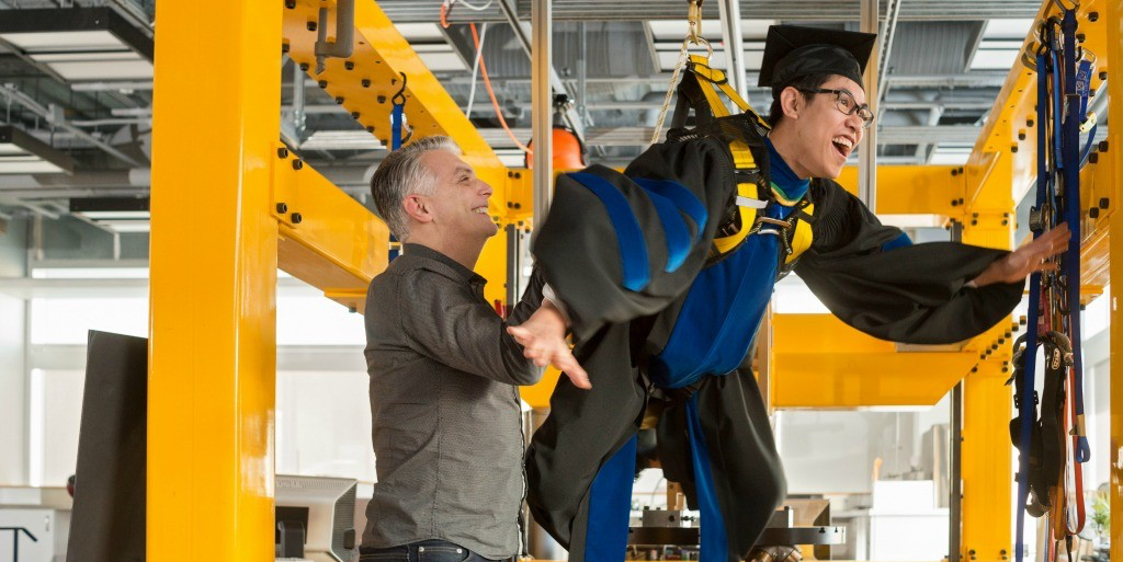 Harnessing potential: Arnold Wong gets uplifted by his PhD supervisor and mentor Greg Kawchuk in the Rehab Robotics Lab. (Photo: Richard Seimens)