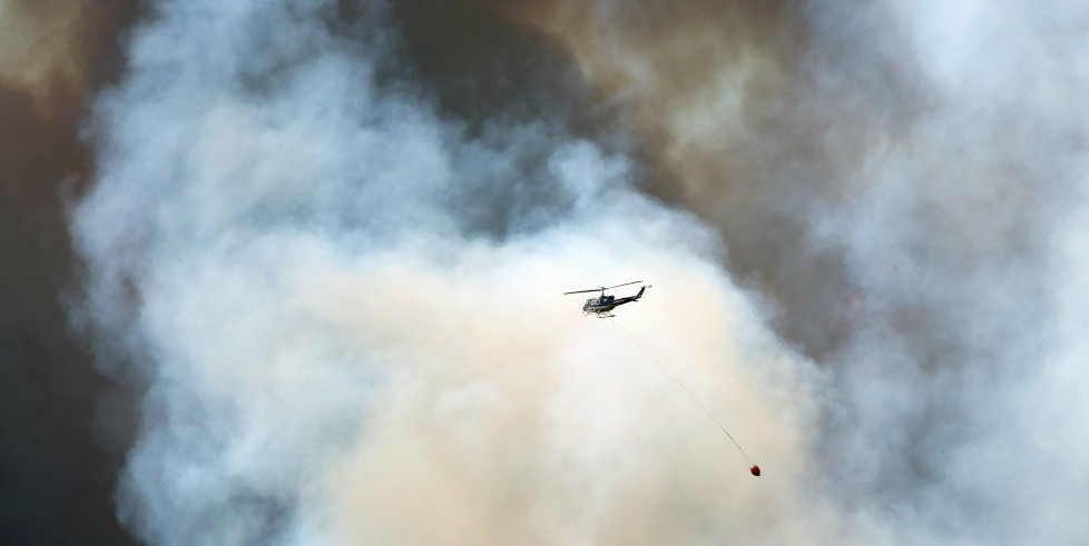 A helicopter carries fire retardant to a wildfire burning in a Fort McMurray neighbourhood on Wednesday, May 4, 2016. (photograph by Chris Schwarz/Government of Alberta)