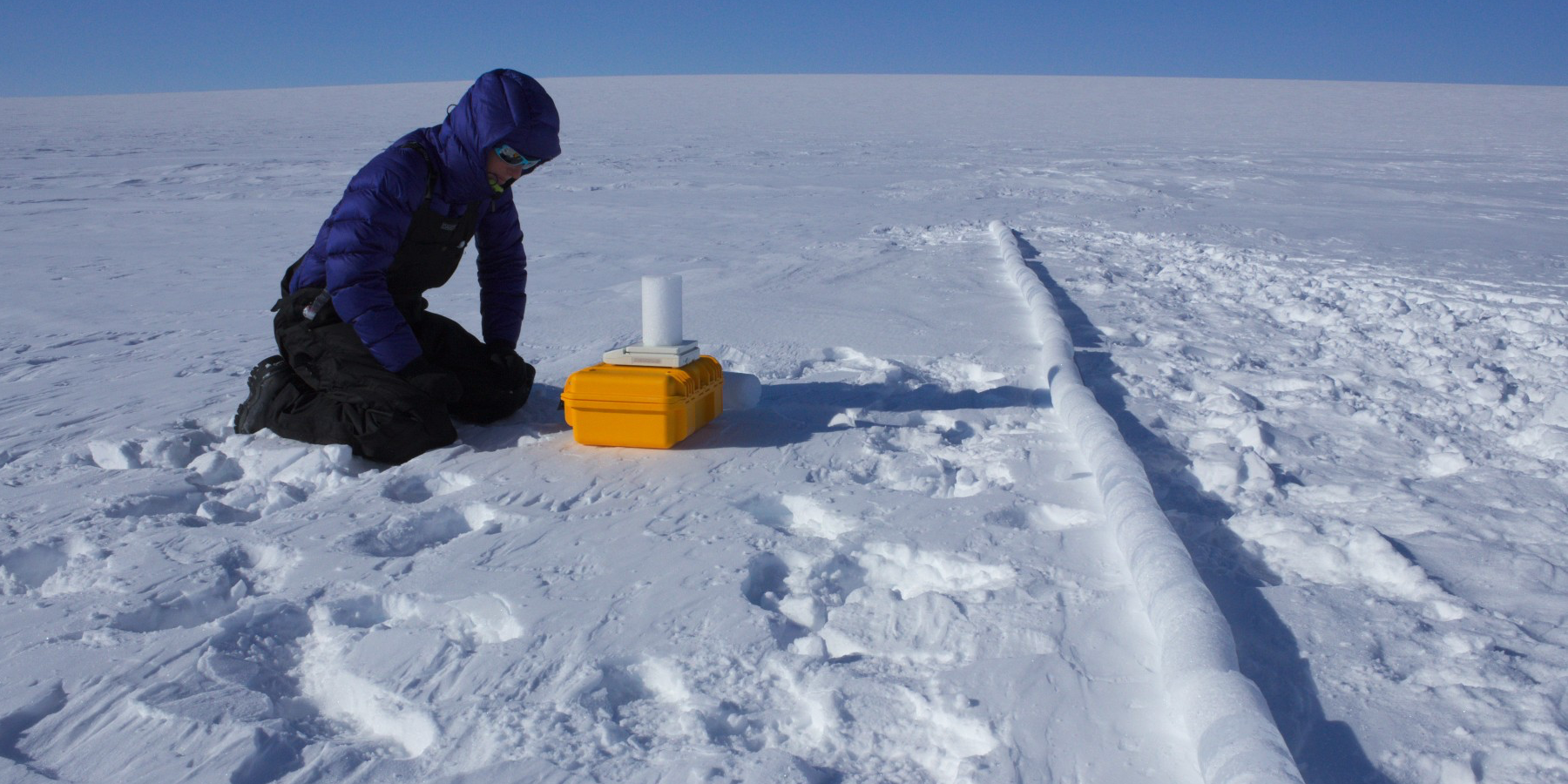 Ice core driller Ali Criscitiello examines a core sample. (Photo courtesy Anja Rutihauser)