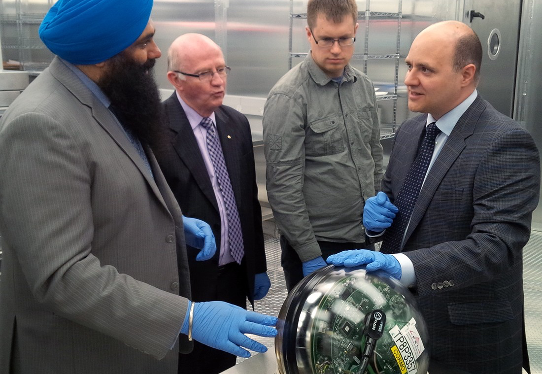 (From left) Minister Tim Uppal, U of A vice-president (research) Lorne Babiuk, and computing science professor Zachary Friggstad listen as Darren Grant demonstrates one of the IceCube digital optical modules during a tour of his astroparticle physics laboratory in the Centennial Centre for Interdisciplinary Science.