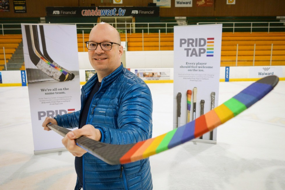 Kris Wells holds a hockey stick wrapped in Pride Tape.
