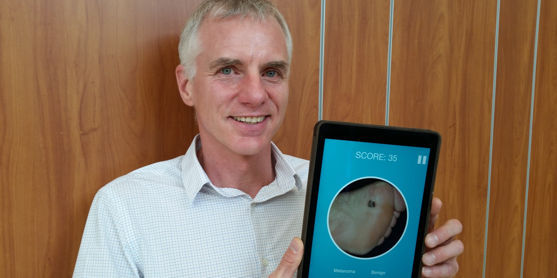 Liam Rourke shows the app that has been developed to help train health professionals to distinguish melanomas from harmless skin lesions.