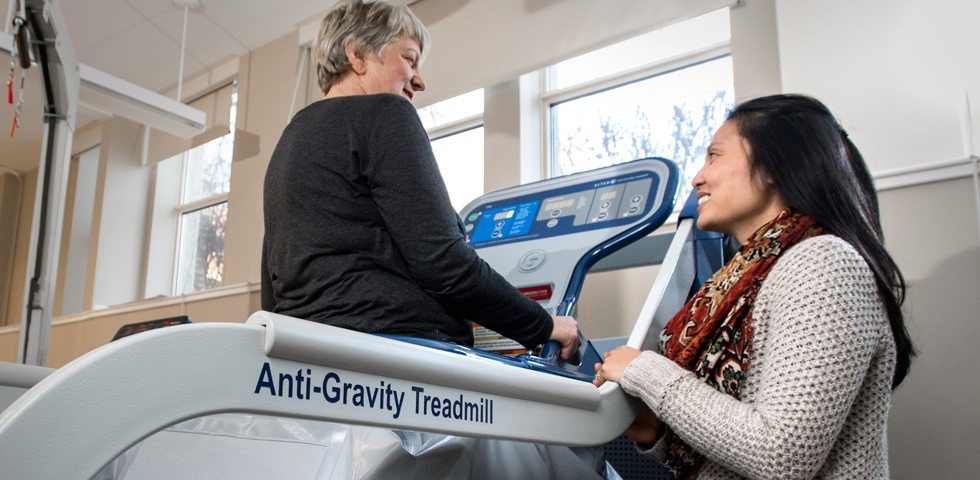 Mariya Oleinikova (left) uses the AlterG anti-gravity treadmill under the watchful eye of physical therapy professor Kim Dao. (Photo: Richard Siemens)
