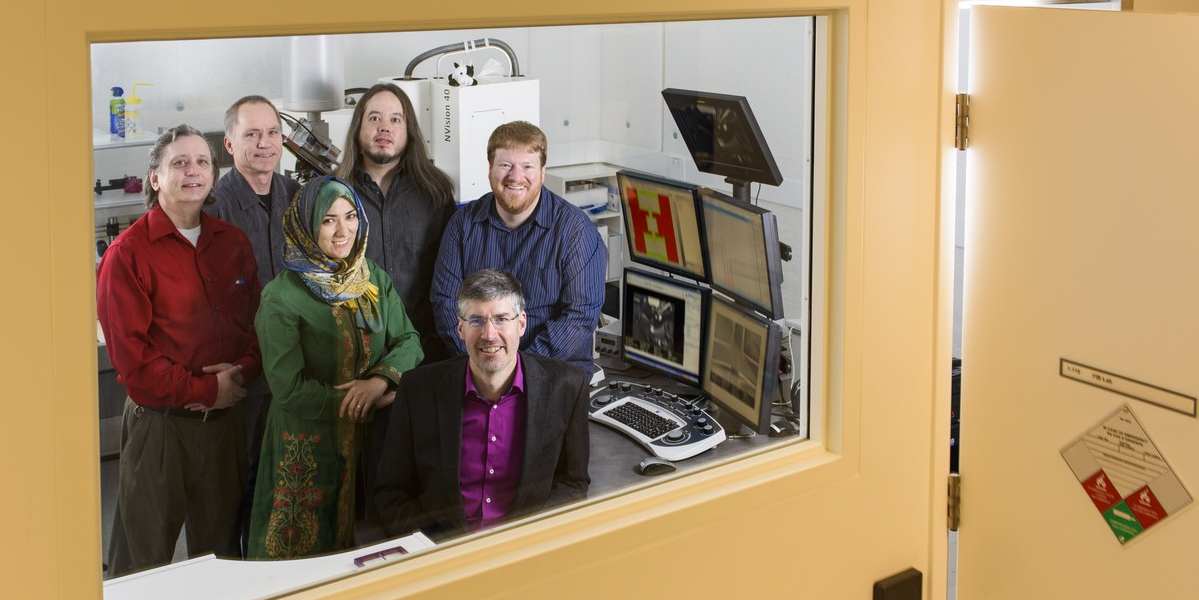 Mark Freeman (seated), with Fatemeh Fani Sani (middle row left), Joseph Losby (top right) and team members have discovered a route to lab-on-a-chip technology for magnetic resonance, a tool to simplify advanced magnetic analysis for device development and interdisciplinary science.