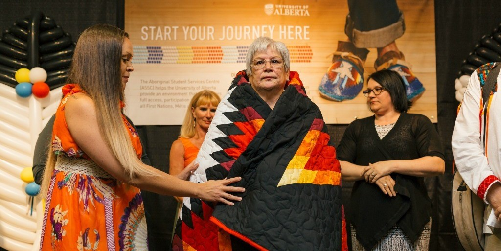 Marilyn Buffalo receives a commemorative star blanket from Aboriginal Student Services Centre director Shana Dion. Adorned with a headdress pattern, the blanket was created by Eunice Ketchemonia-Cote of Saskatchewan to symbolize Buffalo's contributions to supporting Aboriginal students at UAlberta. (Photo: Ryan Whitefield)