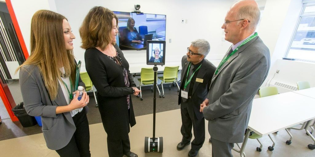 "(From left) New occupational therapy grad Shauna Panton, advanced education minister Lori Sigurdson, vice-provost Nat Kav and Faculty of Rehabilitation Medicine dean Bob Haennel connect with Lisa Jasper, physical therapy co-ordinator at Augustana Campus, via a ""Double Robot."" (Photo: Lyle Aspinall)"
