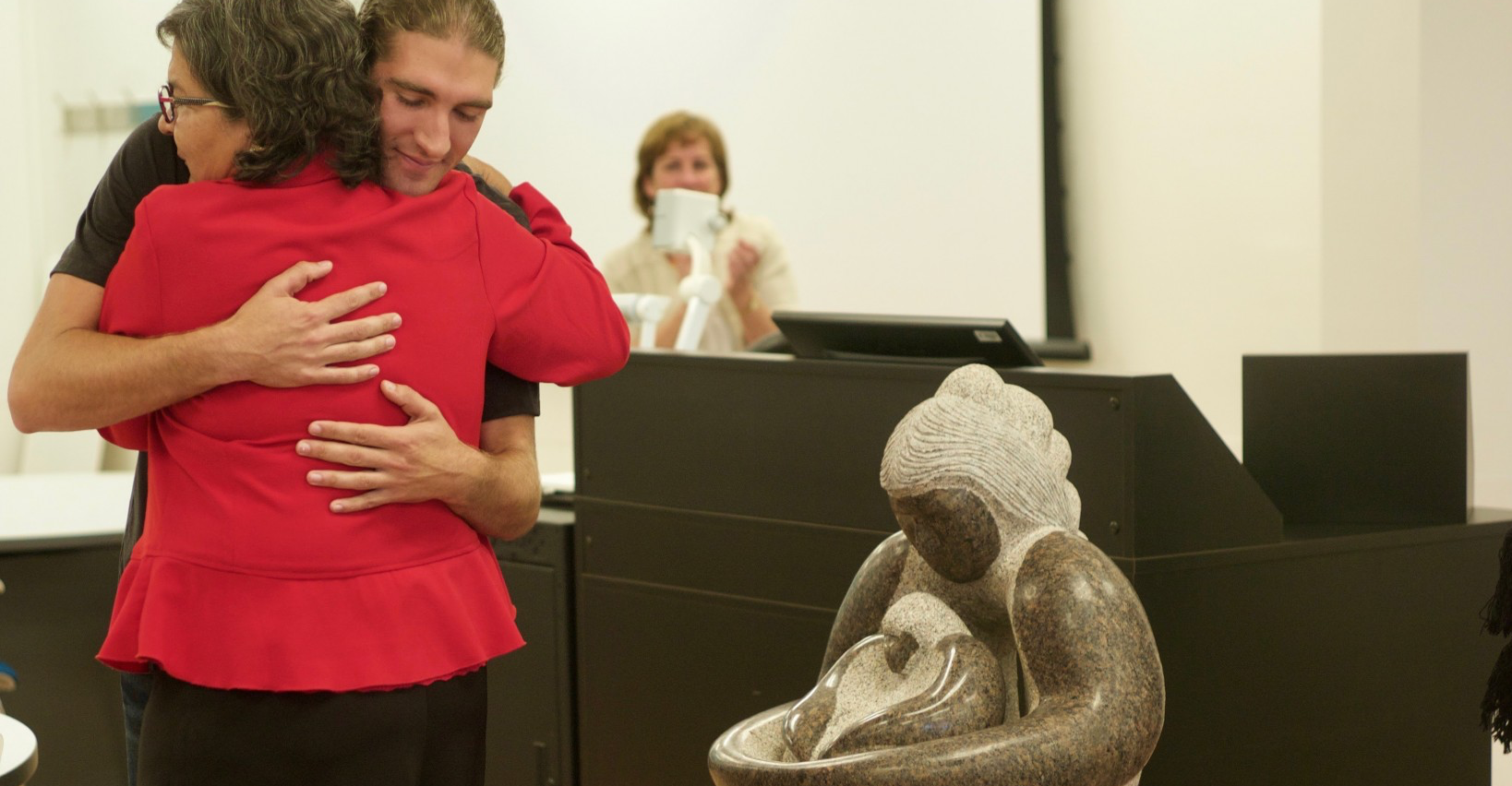 Patricia Makokis and Ben Steinhauer embrace at the unveiling of Eaglechild, a stone carving by Indigenous artist Stewart Steinhauer. (Photo by Michael Lewcio)