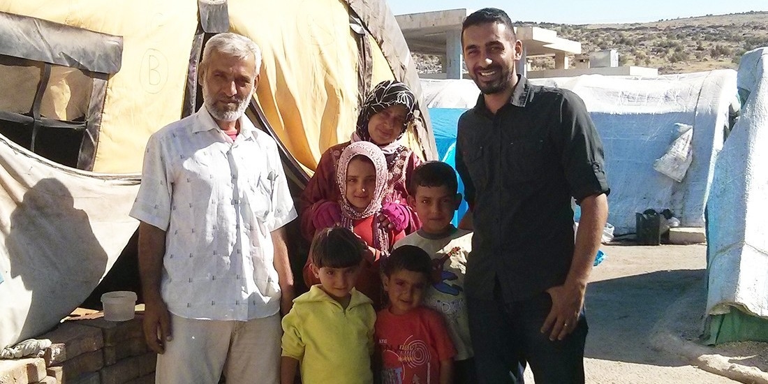 Alumnus Saleem Al-Nuaimi (right) stands with a refugee camp administrator and his family at a camp in northern Syria. Al-Nuaimi's efforts to provide psychiatric support for refugees are just one example of how the UAlberta community is rising to the challenge of a global crisis.