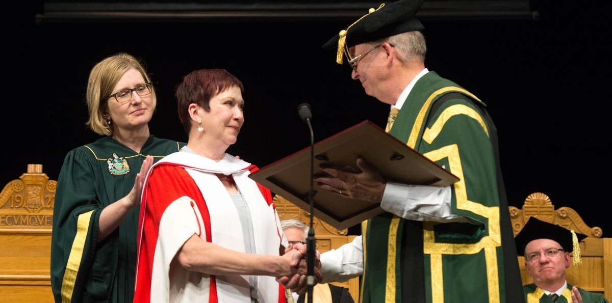 Ruth Kelly is congratulated by Chancellor Ralph Young as she receives her honorary doctor of laws degree June 14. (Photo: Richard Siemens)