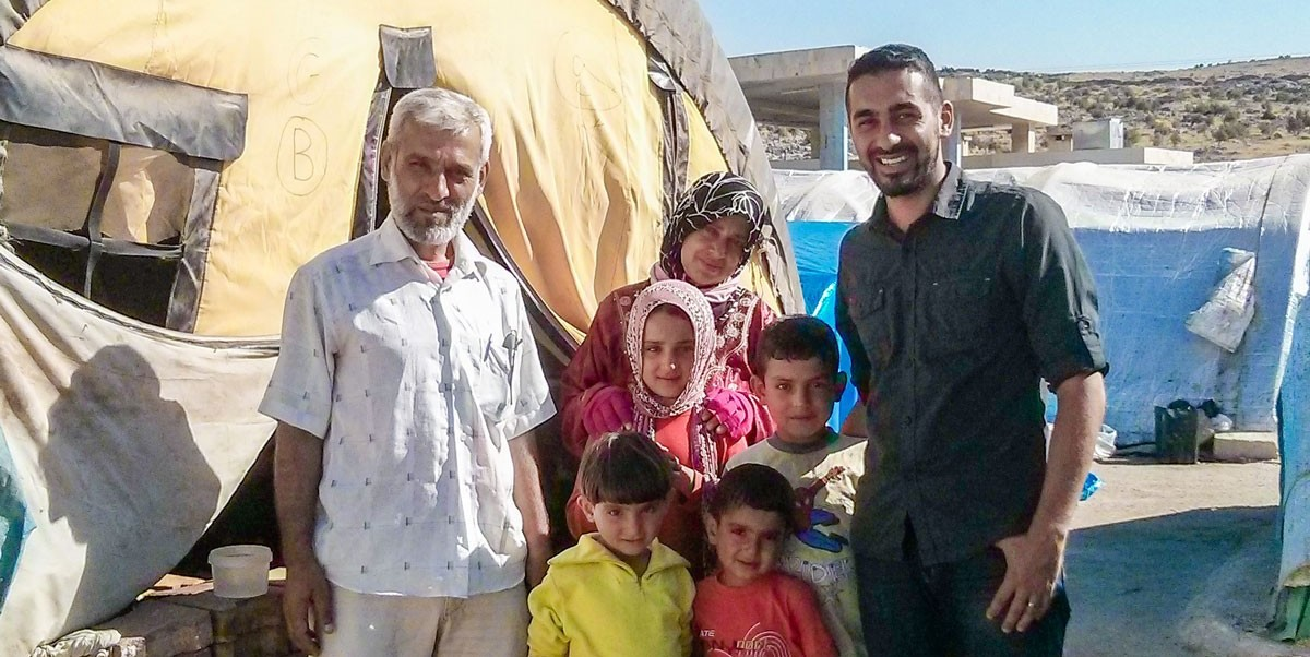 Saleem Al-Nuaimi, right, stands with the refugee camp administrator and his family at a camp in northern Syria in August 2013.