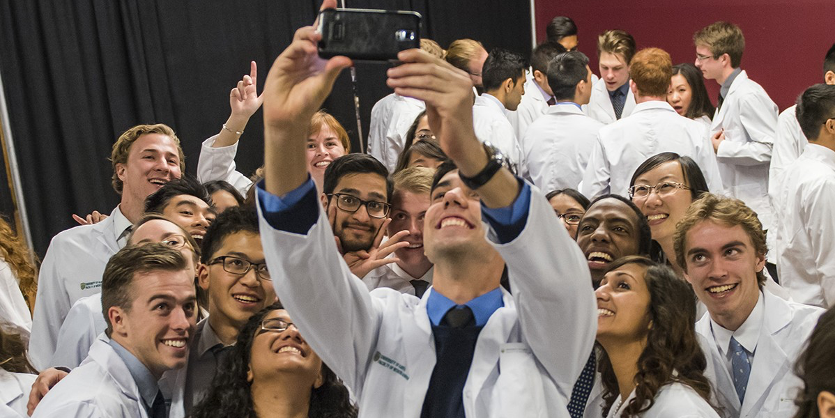 Students snap a selfie at the Dean's White Coat Ceremony.