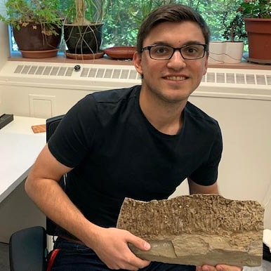 Graduate student Scott Melnyk holds the trace fossil he discovered in the U of A's drill core collection during a sedimentology course. (Photo: Supplied)