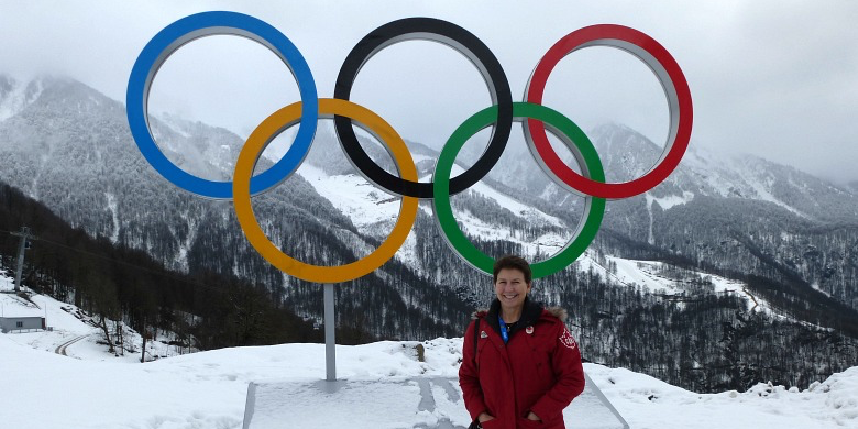 Connie Lebrun stands before the Olympic rings in Sochi, Russia.