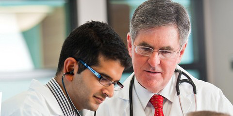 D. Douglas Miller (right), dean of the Faculty of Medicine & Dentistry, and Irfan Kherani (MD '15) work with a patient.