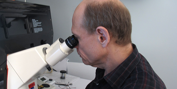 Dr. Michael Hendzel works with a microscope.