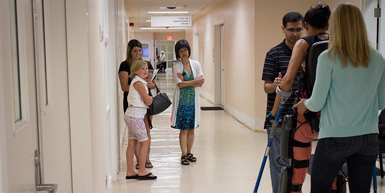 Eight-year-old Cadence Kube and her mom Sarah Clements (left) watch as a study participant with a spinal cord injury walks through the corridors of Corbett Hall using a ReWalk robotic exoskeleton.