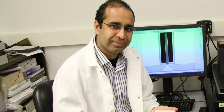 Faheem Khan holds the bimetallic microchannel cantilever, a sensor that can analyze liquids at a smaller volume than was previously possible.