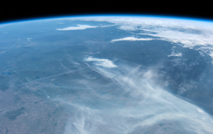 Image of Earth from the International Space Station showing the smoke from the Fort McMurray fire spreading from the fire's leading edges near the centre of the image.
