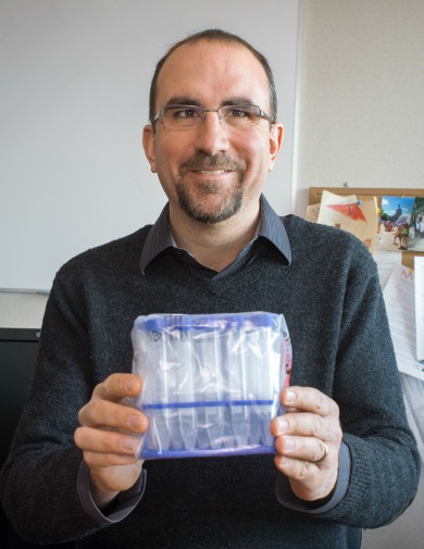 ISTAR director Deryk Beal holds a package of DNA collection kits.