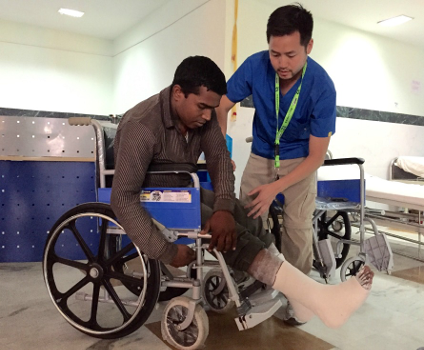 Justin Chan trains an earthquake victim to use a wheelchair in Kathmandu, Nepal.