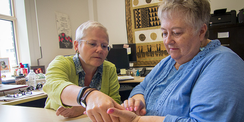Occupational therapy professor Cary Brown (left) shows patient Nancy Cheyne how to apply shiatsu treatment to her hand.
