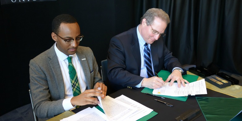 "Provost Carl Amrhein and Students' Union president Petros Kusmu sign the approval of ""Green and Gold Week,"" a new fall break for UAlberta students."