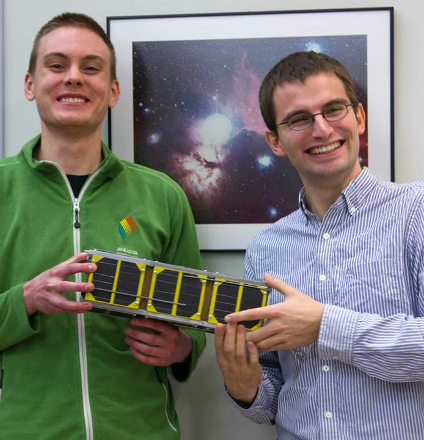 Science alumnus Collin Cupido (left) and engineering student Charles Nokes, project lead, hold a life-size model of the satellite Ex-Alta 1.