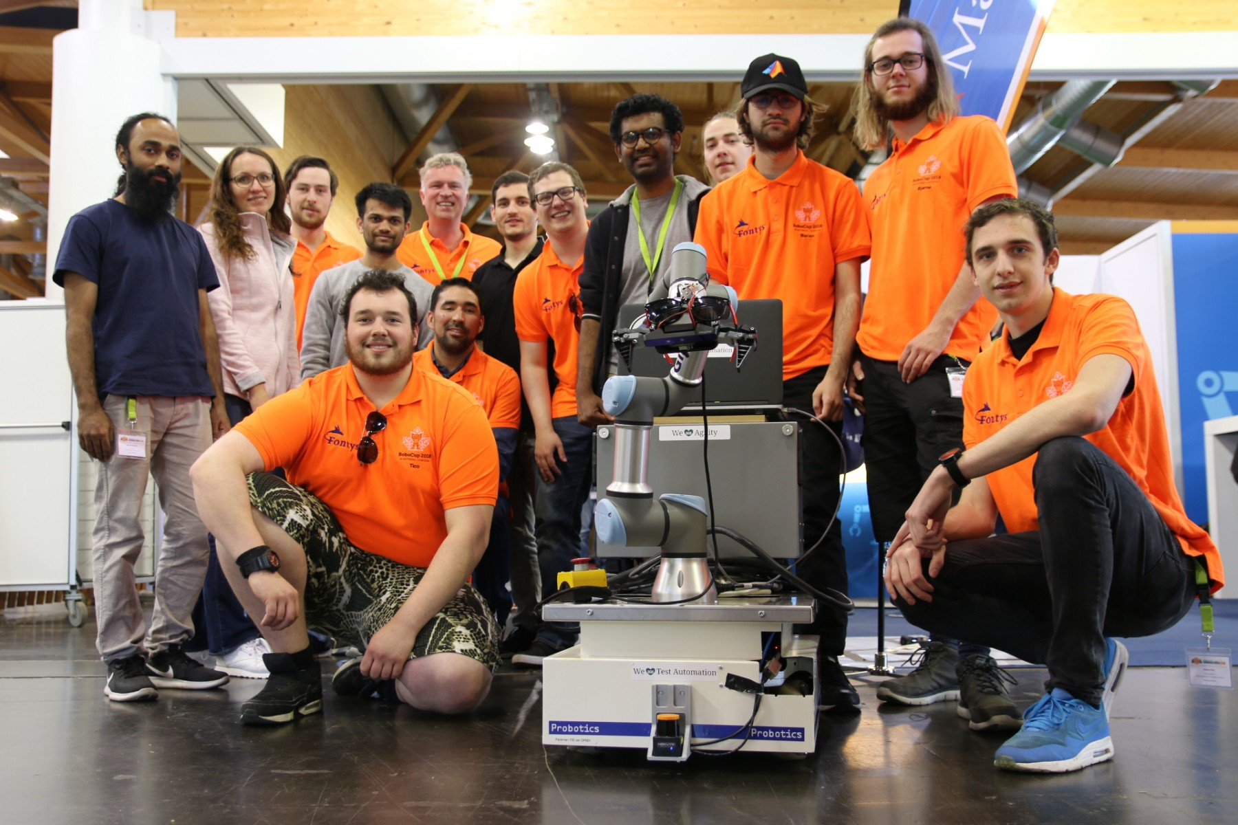 Het team Fontys@Work (in de oranje shirtjes) met robot Faraday. Ronald Scheer is de achterste persoon in het oranje shirt.
