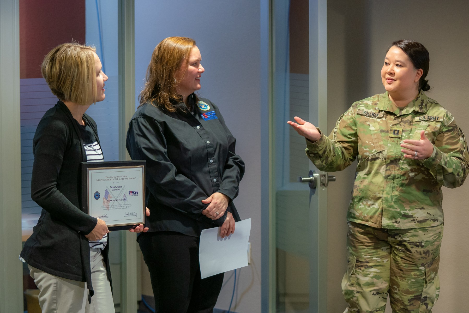 Army Reserve Captain Kayla Voelker (right) shared words of appreciation with her Sourcewell supervisor Anna Gruber (left), as Sourcewell Manager of Human Resources and ESGR volunteer Rebecca Cromwell (center) looked on. Captain Voelker presented Gruber with a Patriot Award at Sourcewell on Feb. 14.