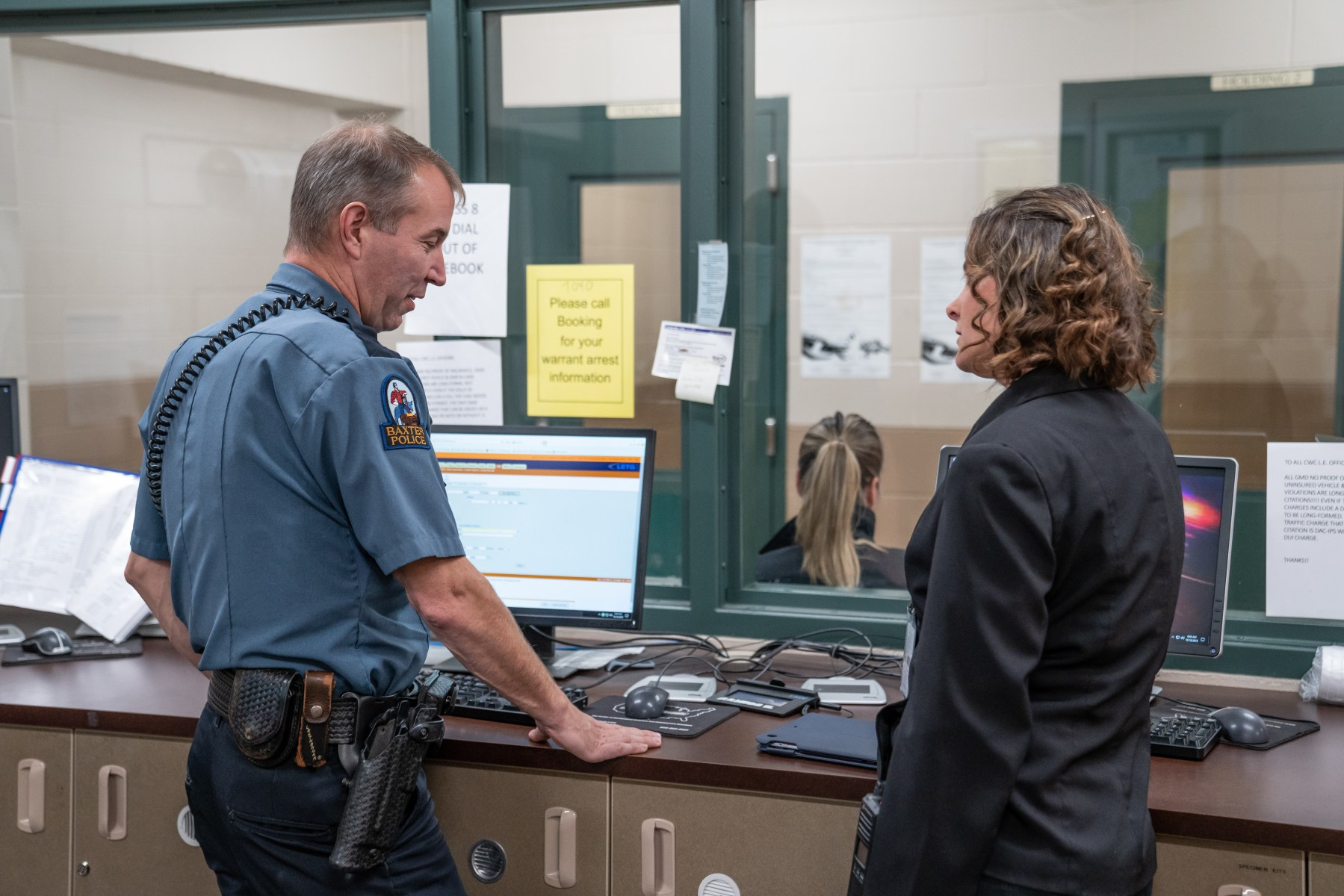 Baxter Police Chief Jim Exsted visits with Theresa Rardin at the Crow Wing County Jail booking room. Exsted said this regional collaboration provides another tool for law enforcement, including jail staff, when dealing with individuals suffering from mental illness.