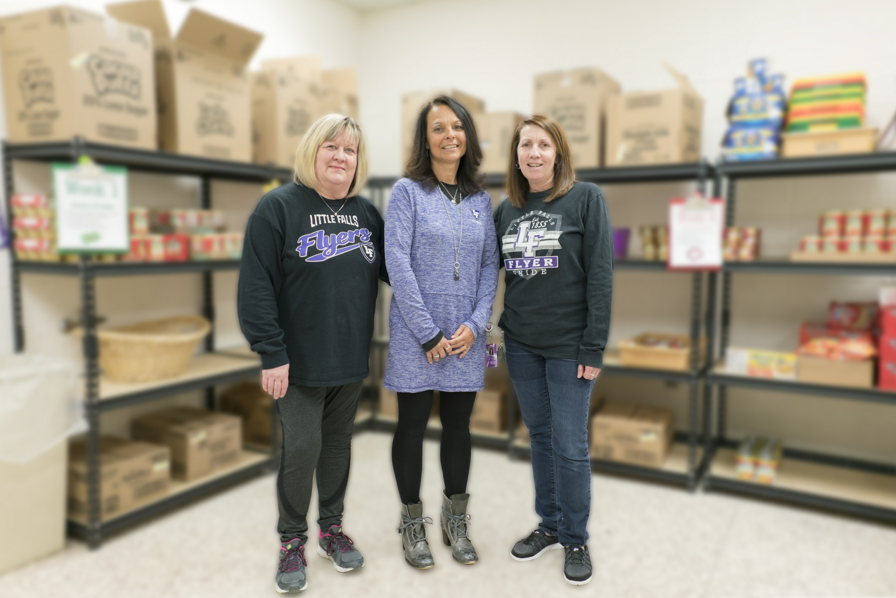 Little Falls educators, Laura DeChaine, Anita Larsen, and Cindy Casillas, stop for a photo as they pack food for students as part of the Flyer Pride Pack Weekend Food Program.