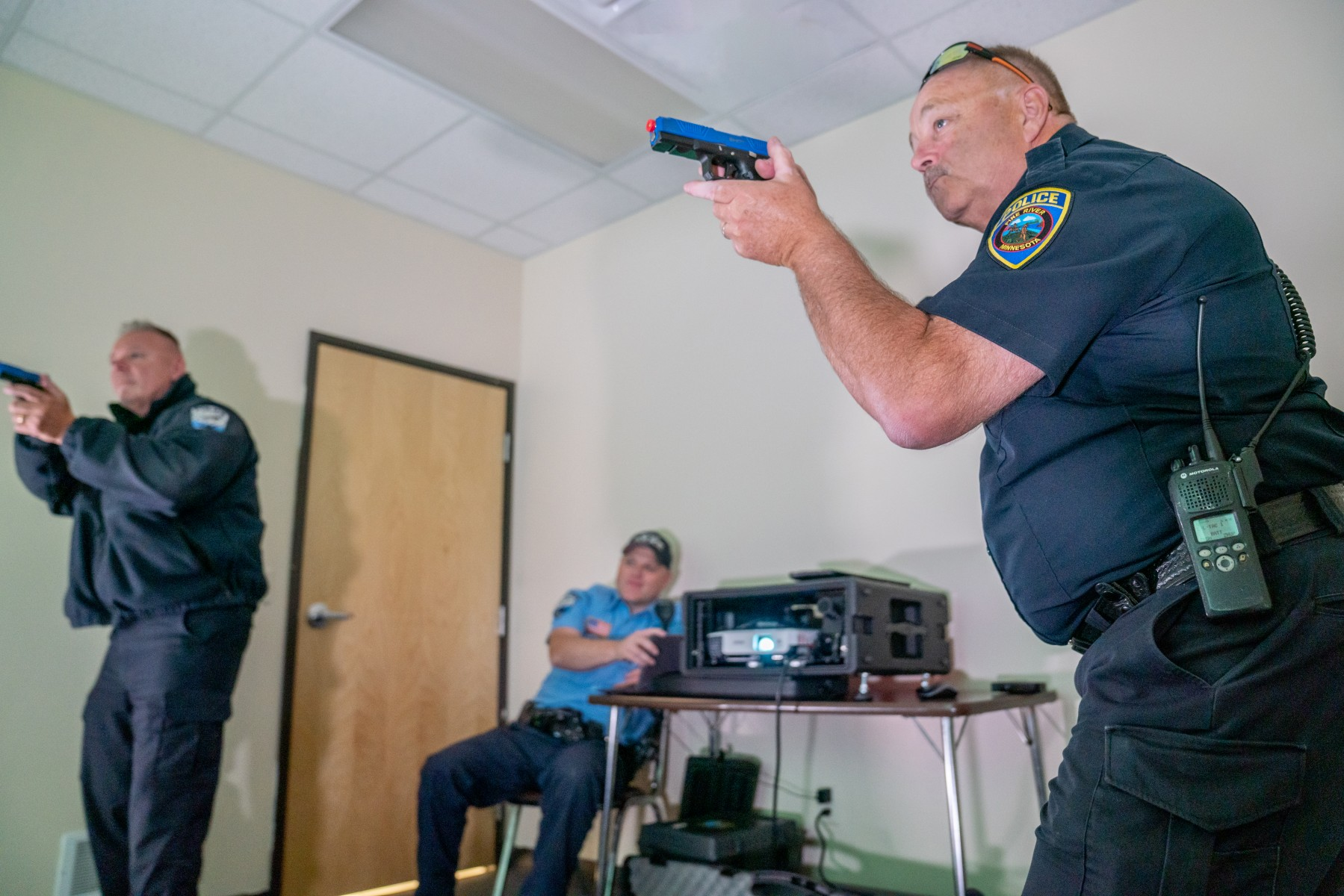 Walker Police Chief Wayne Tennis (left) and Pine River Police Chief Paul Sand train with the Laser Shot Simulator, equipment purchased with Innovation Funding dollars.