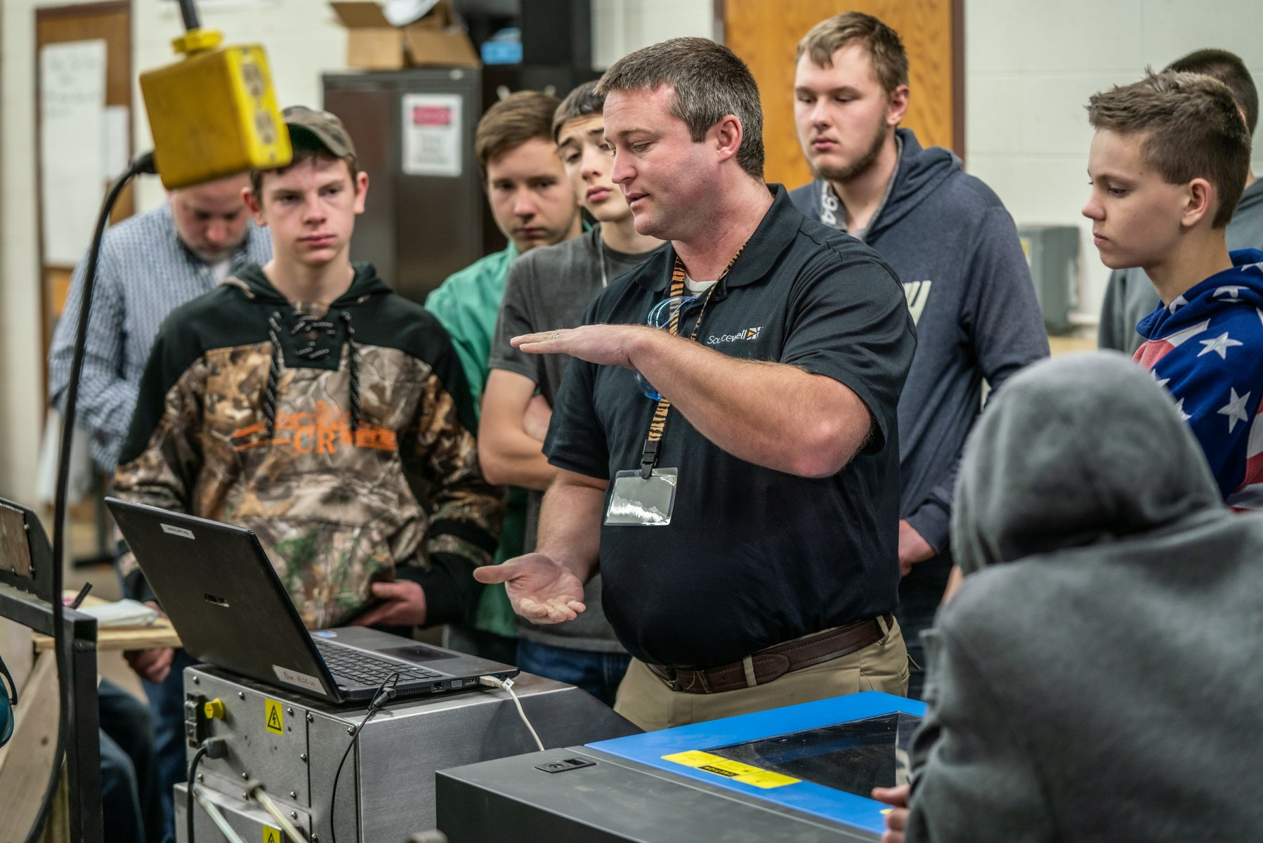 Cutting-edge technology and equipment, including this laser engraver, is available to schools through Tech Mobile. Consultant Aaron Logan demonstrates its capabilities to a welding class at Pine River-Backus High School.