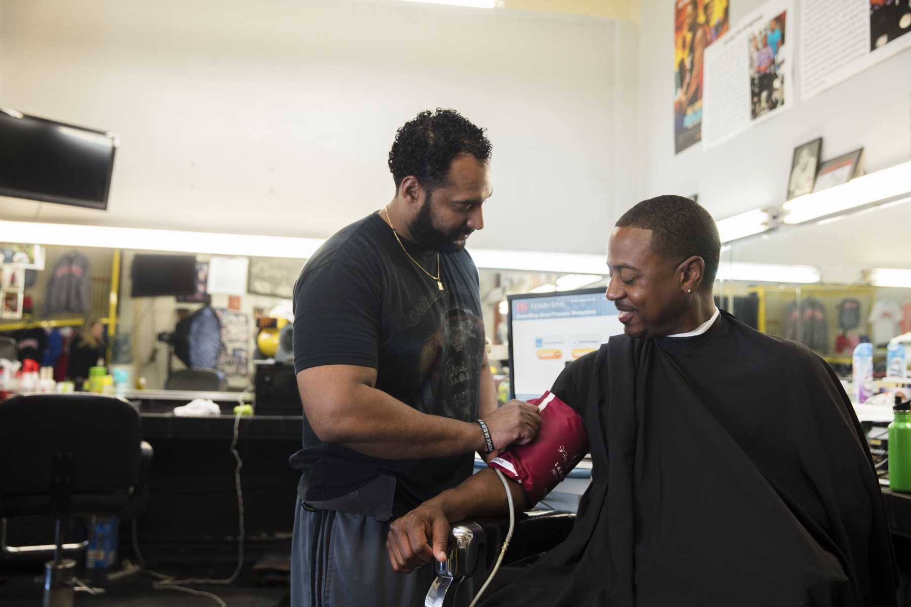 Barber Eric Muhammad takes patron Marc Sims' blood pressure. Photo by Cedars-Sinai.