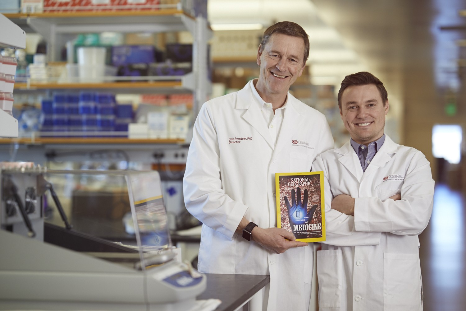 Clive Svendsen, PhD, left, director of the Cedars-Sinai Board of Governors Regenerative Medicine Institute, and Samuel Sances, PhD, a postdoctoral fellow at the institute, with the January 2019 special edition of National Geographic. The magazine cover features a striking image of spinal cord tissue that was shot by Sances in his lab. Photo by Cedars-Sinai.