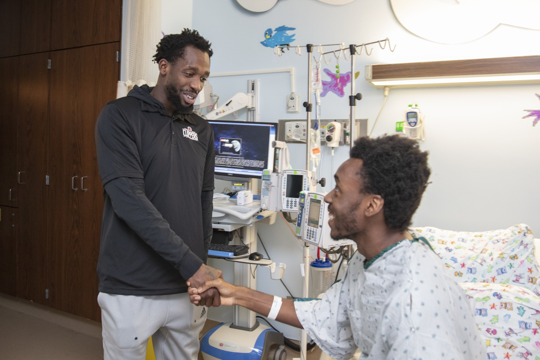 Clippers star Patrick Beverley brightens the day for cancer patient David Mpoupesingul. Photo by Cedars-Sinai.