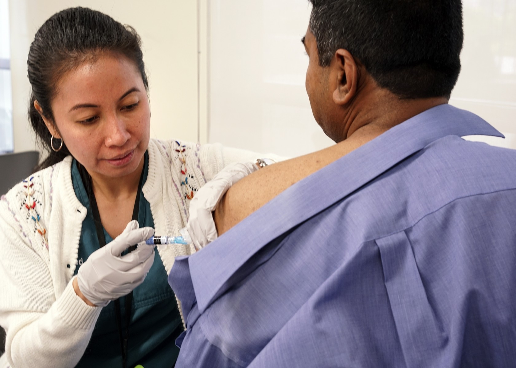 A nurse gives a patient a flu shot. Photo by Cedars-Sinai.